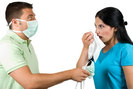 Couple with problems :woman is sick and want to sneeze in a white napkin and the man giving her a protective mask and making a scared face photo