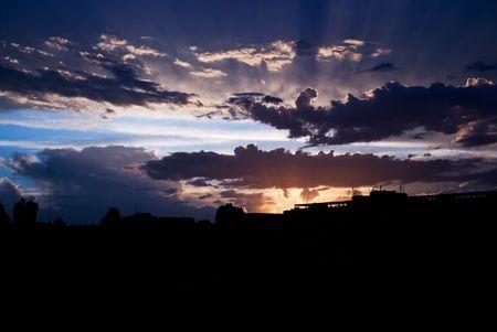 wśród: Promienie słońca na zachodzie słońca wśród chmur przed burza nad miastem silluette Zdjęcie Seryjne