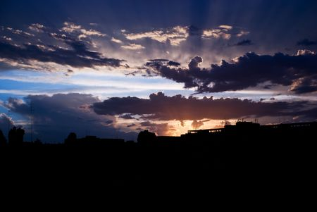 behind the scenes: Rays of the sun at sunset  among the clouds before the storm over city silluette Stock Photo