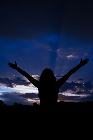 Woman silhouette standing with open hands  to the  storm clouds sky and enjoy the rain and meditating photo