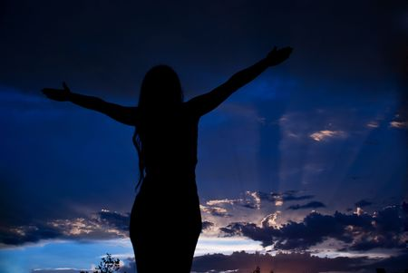 Woman silhouette enjoying  a beautiful evening and open her hands to sky and looking at storm clouds breathe clean air  photo