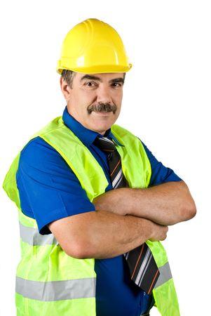 mani incrociate: Ingegnere costruzione giallo che indossa un casco di protezione e maturano in piedi con le mani incrociate e sorridente isolata su sfondo bianco