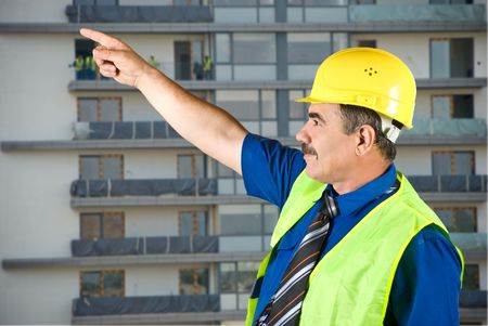 Single mature architect man pointing on site and looking up,construction with workers in background photo
