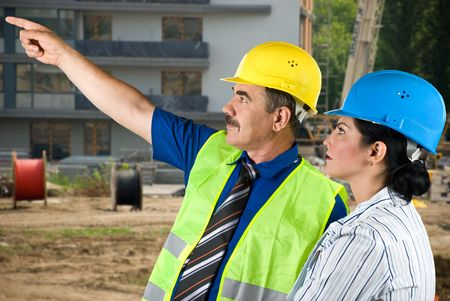Two architects mature man and young woman working on site,the man pointing to somewhere and they have a discussion photo