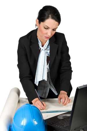 Engineer woman working in her office on laptop and projects and drawing plans with pencil photo