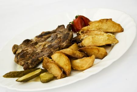 Grilled pork on a plate with garnish of fried potato  with garlic and sliced pickled gherkins Stock Photo - 5228051