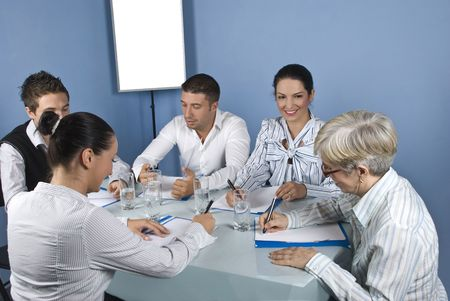 Five business people at meeting have a discussion and they are cheerful and laughing together photo