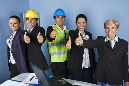 Five engineers team give thumbs up and smiling in a office showing successful in business photo