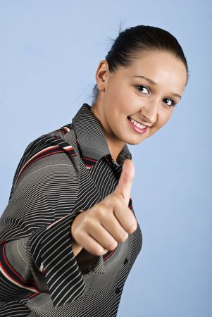 Young business woman give thumbs up and smiling isolated on blue background photo
