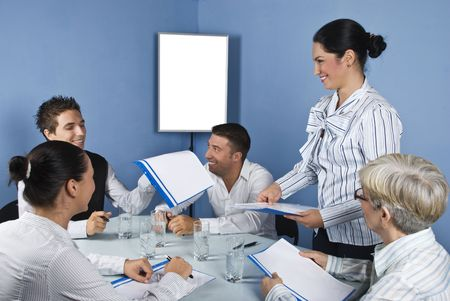 Group of people at meeting having fun and laughing while a business woman giving all folders with papers,blank chart for presentation in background photo