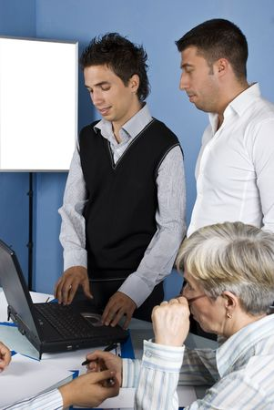 Two business man using laptop at a meeting and other  people have an conversation photo