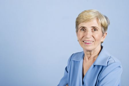 Portrait of senior business woman smiling isolated on blue background ,copy space for text message photo
