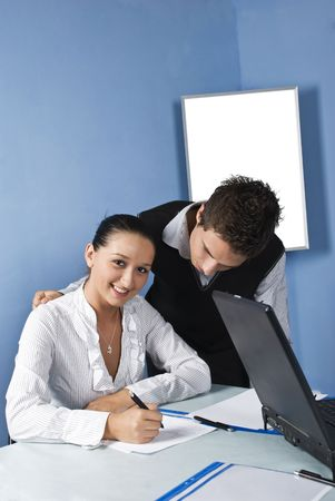 Two young business person  in a office,the man showing her something on paper and the women looking at camera and smile photo
