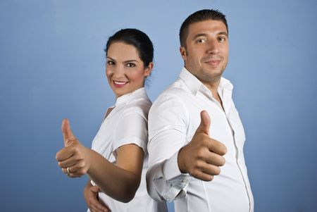 Couple of  business people ,woman and man dressed in white shirts giving thumbs up on blue background photo