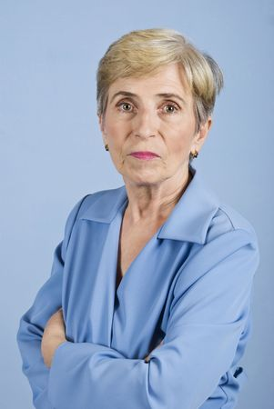 Senior business woman standing with arms crossed  and looking at you isolated on blue background photo