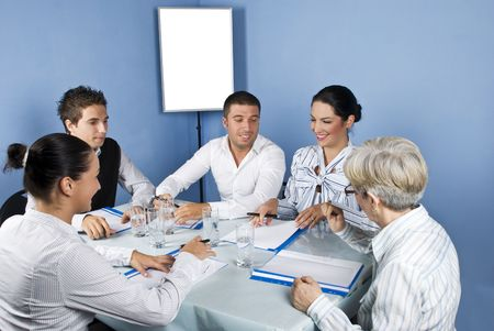 casual meeting: Five business people around a table at meeting laughing together and looking to paperwork of a businesswoman,blank chart or white board in background were you can type your text