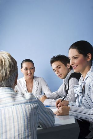 Smiling business people having a meeting and they discussion together on blue background photo