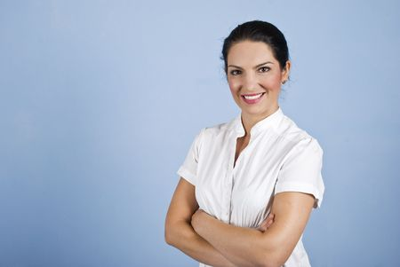 Attractive young business woman standing with arms crossed on blue background,copy space for text in left part of image photo