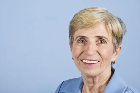 Portrait of smiling senior business woman on blue background,copy space for text message in left part of image photo