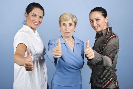 Drie business vrouw, jong en senior geven duimen omhoog en glimlachen geïsoleerd op blauwe achtergrond