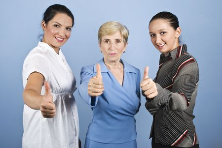 Three business woman,young and senior giving thumbs up and smiling isolated on blue background photo