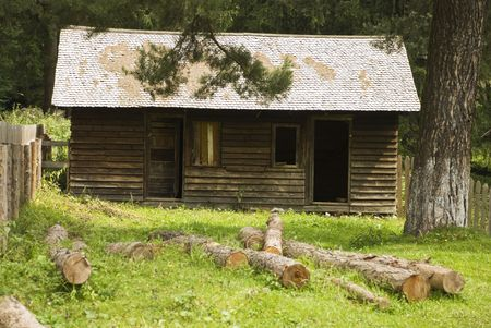 Old wooden house in a village at country with cut trees in the yard photo