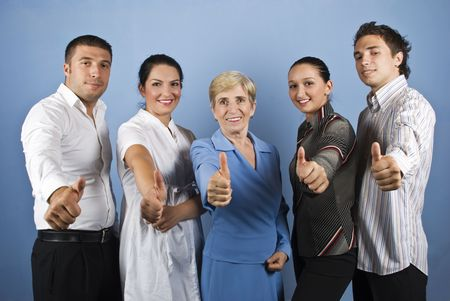 Group of happy business group giving thumbs up and smiling isolated on blue background photo