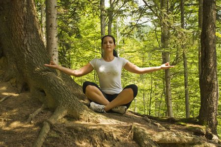 Young woman doing yoga in nature and sitting in lotus position near a tree in forest,breating the clean air of mountains photo