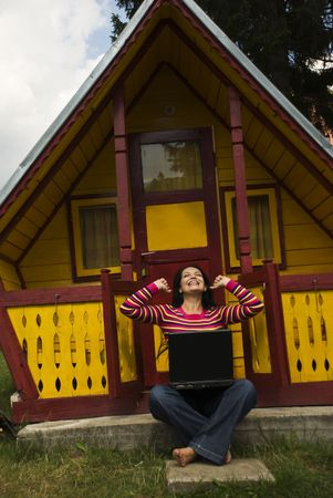 maisonette: Beautiful ecstatic woman using laptop and being very happy of her successful business work in vacation