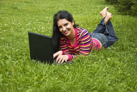 Beautiful brunette woman in colorful clothes and jeans and barefoot laying on green grass in nature and using her laptop photo