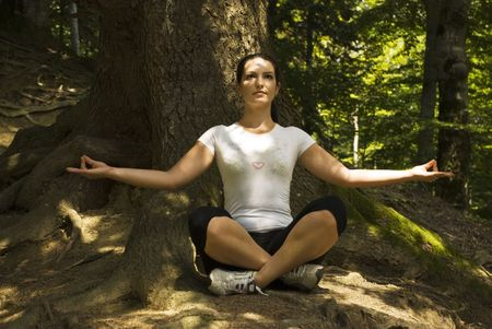 Woman doing yoga and standing in lotus position  in forest with rays sun on his face and body photo