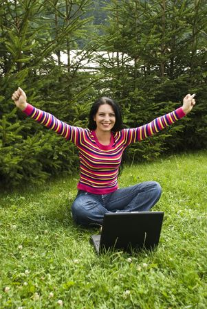 Victorious and excited young woman using laptop outdoors in vacation and being very happy about her success business photo