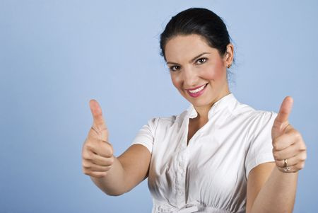 Beautiful business woman giving thumbs up on blue background,copy space for text message in left part of image photo