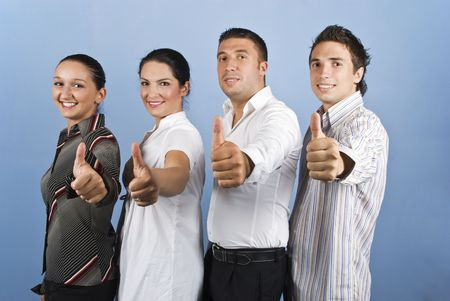 Four young business people team standing in a line and giving thumbs up  photo