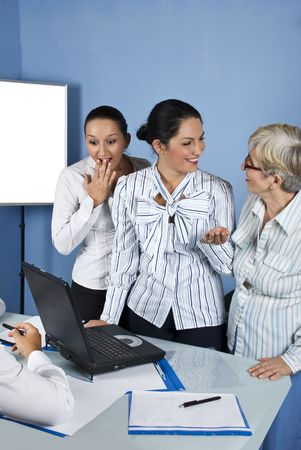 A surprised business young woman looking to laptop and the other two women laughing together ,they all having a meeting in a office photo