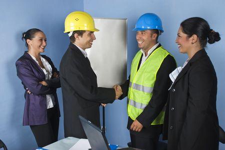 manos estrechadas: La mano dando dos hombres arquitecto batidos y la mujer ingeniero reír juntos y divertirse