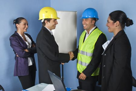 Two architect mens giving  hand shakes and  engineer woman laughing together and having fun photo