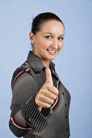 Portrait of young business woman smiling and giving thumb up on blue background photo