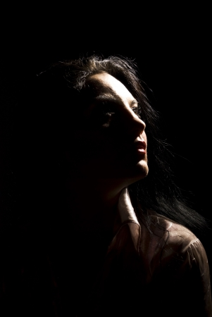 Portrait of beautiful brunette woman looking away in darkness  with soft light on her face photo