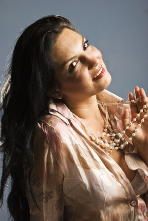 Portrait of sensual brunette woman looking at camera and holding pearls with her fingers,back light and softness lighting on face photo