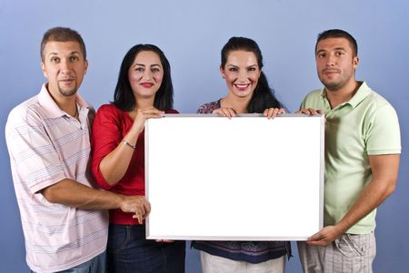 Four mid adults friends 30-34 years age holding a white blank banner and smiling together on blue background,copy space for text message on card photo