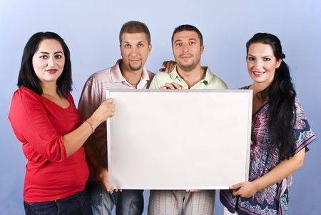 Four friends standing in a line and holding a blank banner for presentation on blue background Stock Photo - 5464706