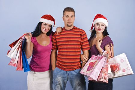 Three friends at shopping holding Christmas presents,women smiling and wearing red hats photo