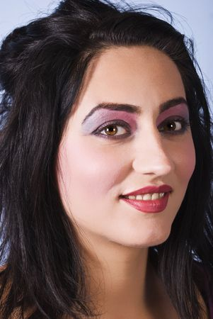 Close up of beautiful mid adult female face with pink-mauve make up eyes and red lipstick smiling photo