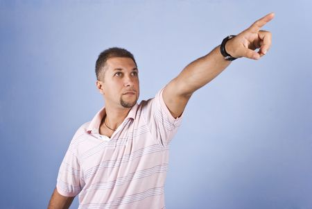 Mid adult man with pointing hand to copy space and looking up on blue background photo