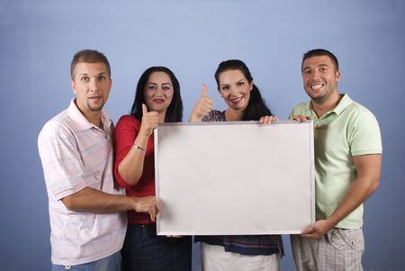 Four happy friends holding a blank banner and giving thumbs up on blue background photo