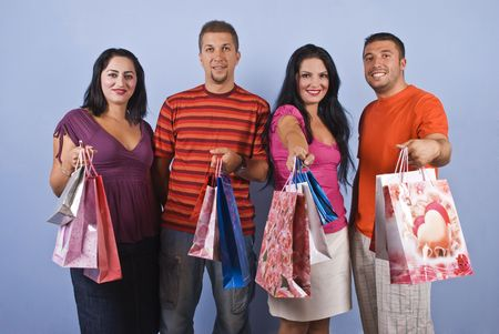 Group of happy friends,two couples  having fun at shopping and they holding bags in their hands on blue background photo
