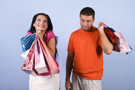 Naughty vanity woman laughing and peeking men,she having fun and it is excited of shopping bags while the man it is tired ,bored  , looking down and  holding some bags on his back Stock Photo - 5469113