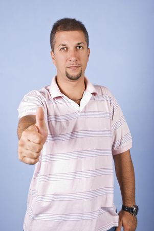 Portrait of mid adult man with beard giving thumbs up on blue background photo