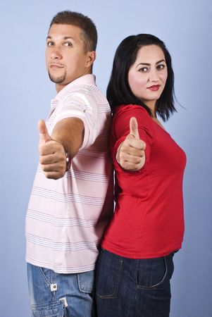Cheerful couple giving thumbs up and standing back to back on blue background photo